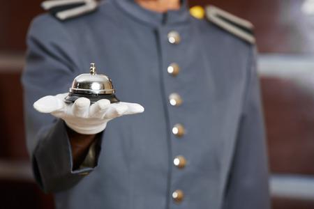 Hotel bell op de hand van een hotel receptionist bij de receptie