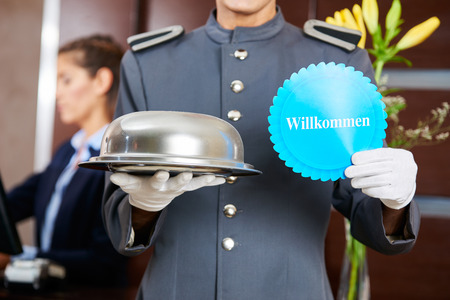 willkommen: Hotel page holding German sign saying Willkommen (welcome) Stock Photo