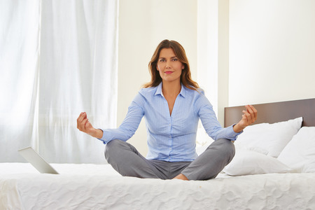 hotel room: Businesswoman doing yoga in hotel room on bed for relaxation Stock Photo