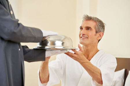 Hotel page bringing food as room service to an elderly man in a hotel room Stock Photo