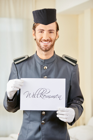 Smiling hotel page holding German sign saying Willkommen (welcome)