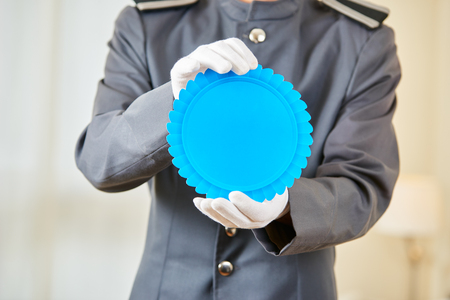 hospitality staff: Hotel marketing with blue badge held by a hotel clerk