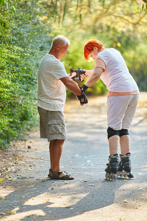 Senior woman learning to skate with her husband in the park Stock Photo