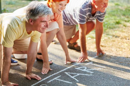 Senior friends at the starting point of a race in summer in the park Stock Photo
