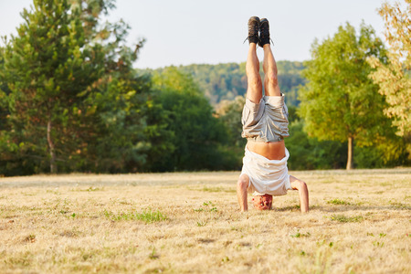 activ: Activ senior man making a headstand in summer in the park