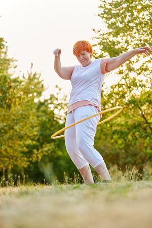 Aktywny senior kobieta podczas treningu fitness w parku z obręczą