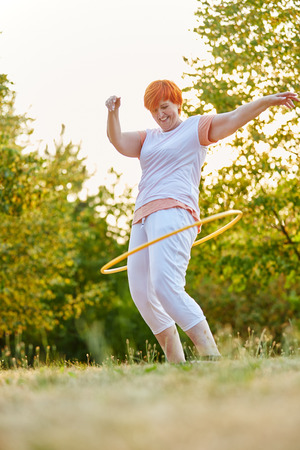Mujer senior activa durante el entrenamiento de fitness en el parque con un aro