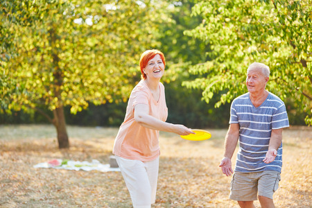 play the old park: Happy senior couple playing flying disk in summer in the park Stock Photo