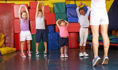 Kids gymnastiek met groep kinderen in de lichamelijke opvoeding met PE leraar