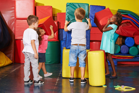 preschool children: Many children helping together to tidy up in a preschool gym Stock Photo