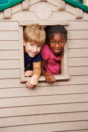 playhouse: Two happy children looking together through a window in a playhouse Stock Photo