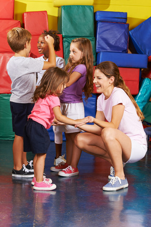 physical education: Happy children exercising with nursery teacher in gym of a kindergarten Stock Photo