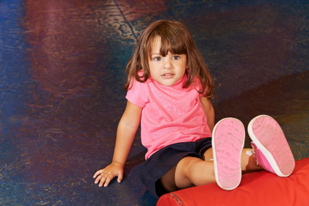 elementary schools: Little child doing children sports in gym with her legs on a pillow