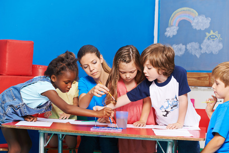 Children painting with brush and water color in kindergarten at table