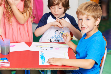 art lessons: Boy painting image with water color and brush in elementary school