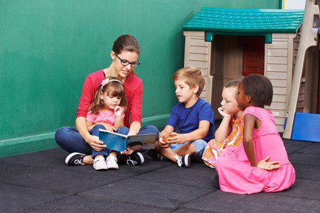 Nursery woman reading book for group of children in a kindergarten Stock Photo