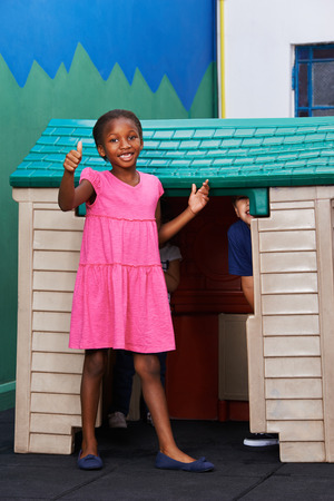 children at play: African girl holding thumbs up in kindergarten in front of a playhouse Stock Photo
