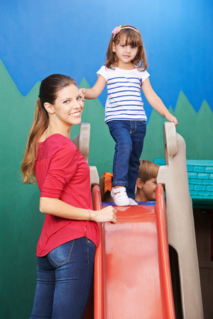 Mother standing with daughter on slide in a nursery photo