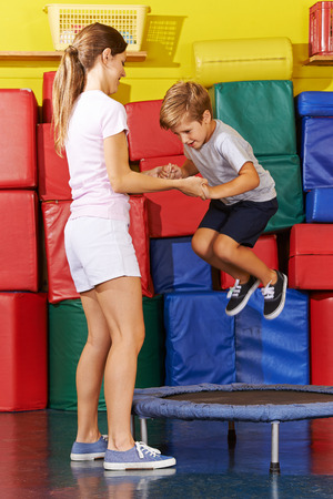 Boy jumping on trampoline in gym with help of PE teacher photo