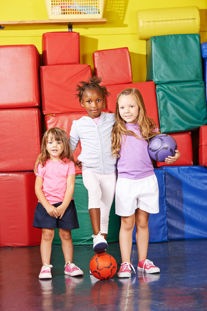 Three kids playing soccer in gym together in preschool photo