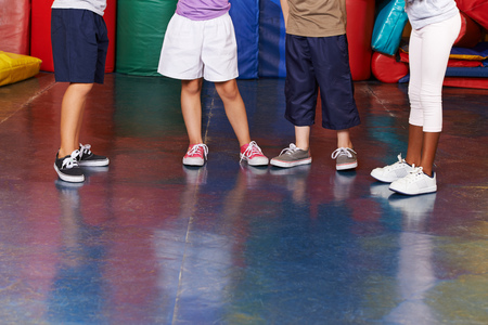 Many legs with shoes of different children in a gym photo