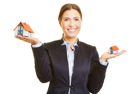 woman shop: Smiling real estate broker holding two small houses on her hand Stock Photo