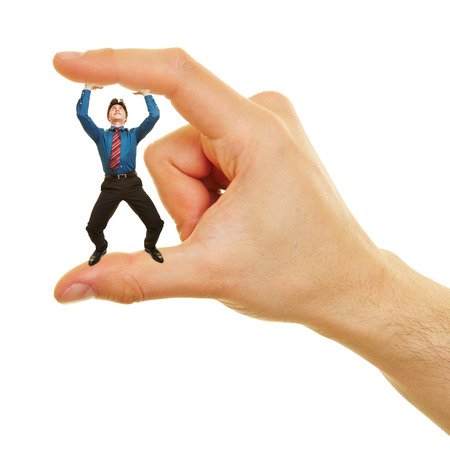strenuous: Small business man standing between two fingers