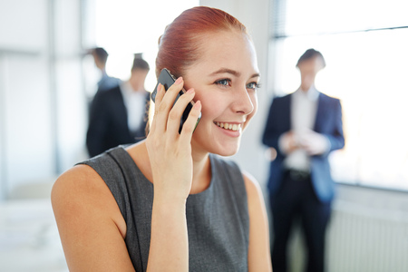 Successful businesswoman calling on the phone listening to good news Stock Photo