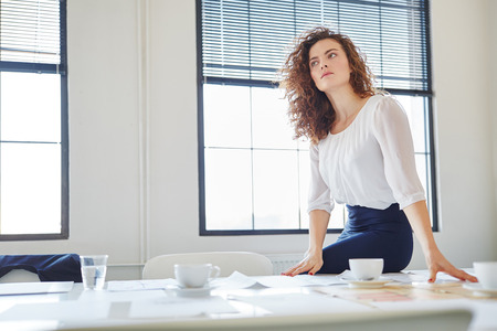 founder: Woman as entrepreneur with vision thinking in start-up office Stock Photo