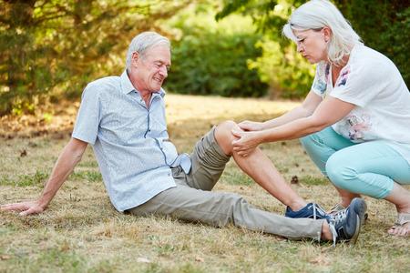 Vrouw oefenen eerste hulp op de knie van een oude man en zet een pleister op het Stockfoto