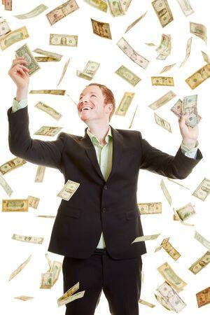 money rain: Happy businessman catching dollars under a dollar rain