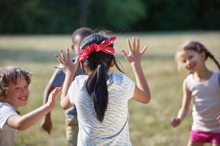 finding out: Happy kids playing blind mans buff at a birthday party