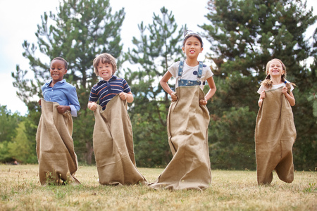 Children competing at sack race at the park