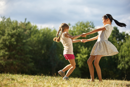 hand movement: Two girls dancing in a circle in summer and have fun