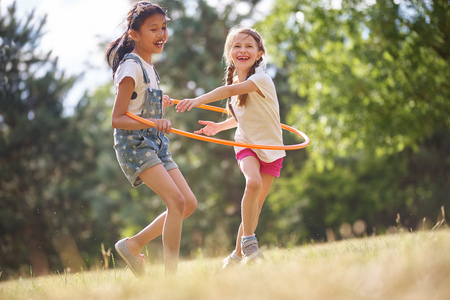 Two happy girls play with hula hoop in summer