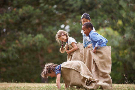 Group of interracial kids competing at sack race
