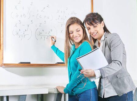 university: Student ant teacher solve a math problem on the blackboard