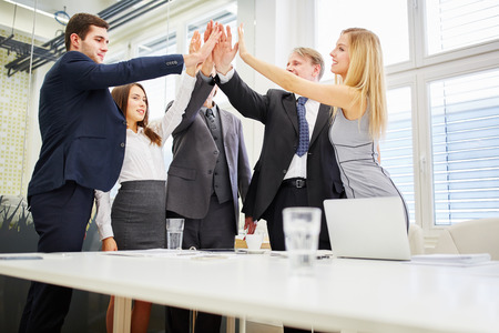 motivation: Business team high fives each other in the office for motivation Stock Photo
