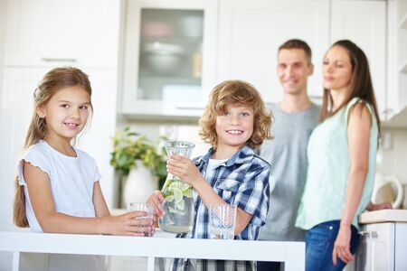 Two kids with carafe drinking fresh water with lime in the kitchen