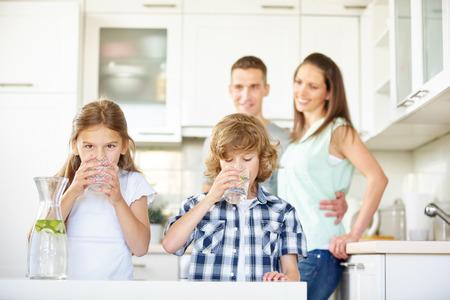 Jungen und Mädchen trinken Wasser mit Kalk in der Küche, während die Eltern beobachten