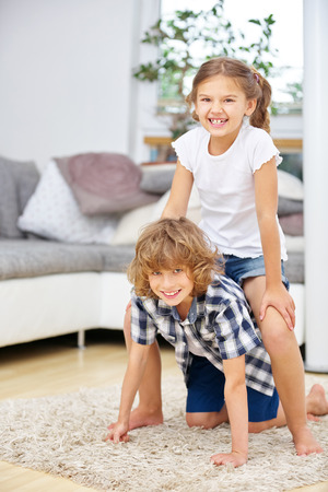 romp: Two happy children playing at home in the living room