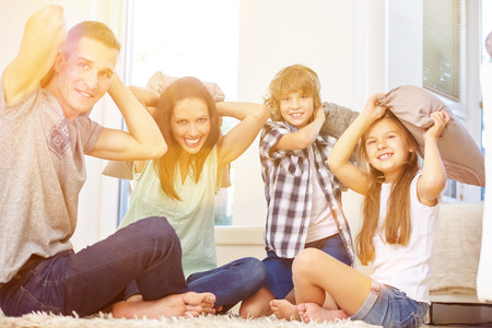 romp: Happy family and kids having pillow fight at home in the living room