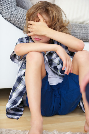 disobedience: Defiant boy in bad mood holding hand over his eyes at home Stock Photo