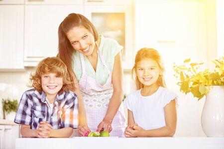 niños desayunando: madre y los niños de corte fruta de la cal en la cocina para el desayuno Feliz Foto de archivo