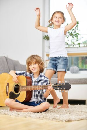 boy playing guitar: Girl dancing to music from boy playing guitar at home