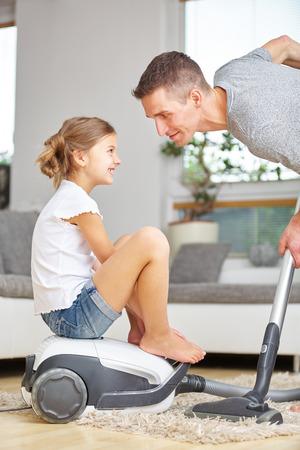 父の真空掃除機に座っている女の子を自宅でクリーニング
