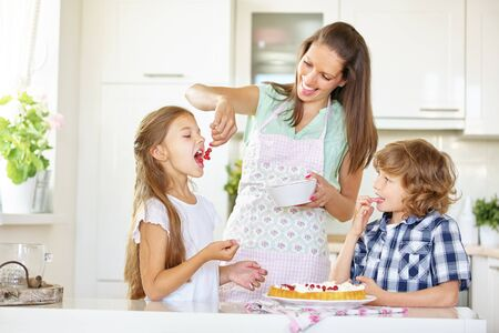 childrens food: Mother and children baking cake together with red currants in the kitchen