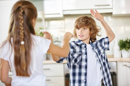 Children fighting with wooden spoons in jest in the kitchen Stock Photo