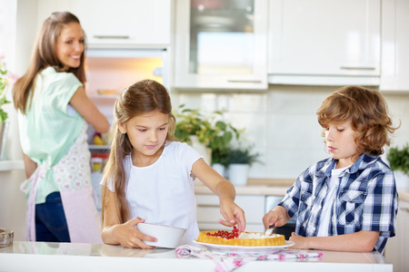 Children baking fruitcake with red currants in the kitchen photo