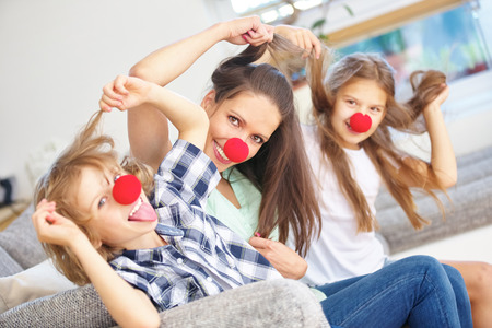 Mother and kids being crazy at home with red noses and wild hair photo